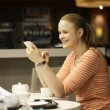 Young woman chatting on smartphone in cafe. — Stockfoto