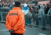 Back security guard in front of blurred crowd — Stock Photo