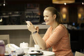 Young woman chatting on smartphone in cafe. — Stock Photo