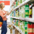Young woman shopping for juice in supermarket — Stock Photo