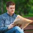 Man reads newspaper on bench in the park — Stock Photo