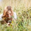 Girl is writing sms on the phone lying in grass — Stockfoto