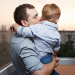 Father kisses his son on the balcony — Stock Photo #30102959