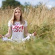 Stock Photo: Young girl meditating in field