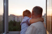 Grandfather and grandson embracing on the balcony — Stock Photo