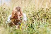 Κορίτσι γράψιμο sms στο τηλέφωνο που βρίσκεται στο γρασίδι — Φωτογραφία Αρχείου