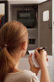Young woman rewrites the electrical meter readings — Stock Photo