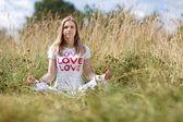 Mladá dívka, meditoval v poli — Stock fotografie