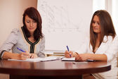 Two women taking notes at a business presentation — Foto de Stock