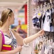 Young mother shopping for childrens clothes — Stock Video