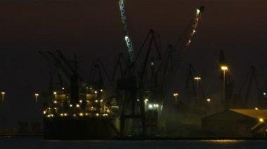 Nacht uitzicht op een haven in een haven met een verlichte vrachtschip — Stockvideo