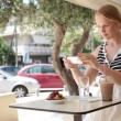 Attractive woman taking picture of a pastry on her smart phone as she sits at a table — Stock Video