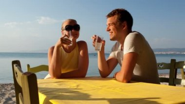 Young couple enjoying drinks at the seaside — Vídeo de stock