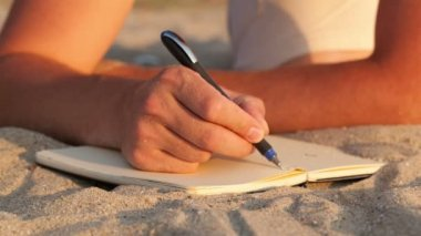 Man writing in his diary at the beach — Stock Video