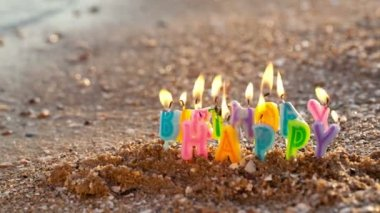 Colourful birthday candles burning on a seashore at the edge of the sea — Stock Video