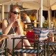 Happy woman wearing sunglasses relaxing in a deckchair in the sun talking on her smart phone — Stock Video