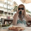 Young blonde woman having a meal in an outdoor restaurant — Stock Video #34188929