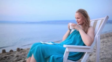 Woman enjoying a cup of tea at the seaside sitting relaxing on a deckchair — Stock Video