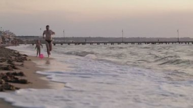 Father and his little son running along the beach playing ball — Stock Video