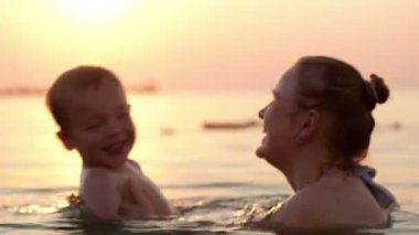 Loving mother and her young child bathing in the sea water — Stock Video