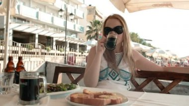 Young blonde woman having a meal in an outdoor restaurant — Stock Video