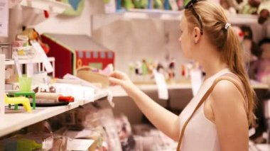 Young woman is choosing toys for her kid — Stock Video