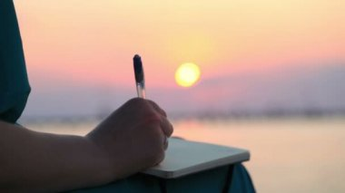 Close up view of the hand of a woman writing in her diary at sunset — Stock Video
