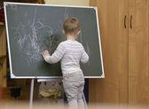 Little boy drawing on a chalkboard at kindergarten — Stock Photo