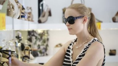 Young woman in sunglasses choosing summer shoes in the shop — Stock Video