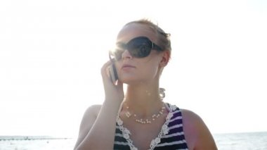 Smiling young woman in sunglasses talking on the phone — Stock Video