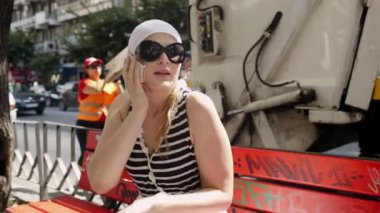 Young woman in sunglasses and white kerchief takes a call — Stock Video