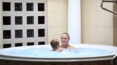 Mother enjoying a spa bath with her son in a bubbling circular jaccuzzi style tub — Stockvideo