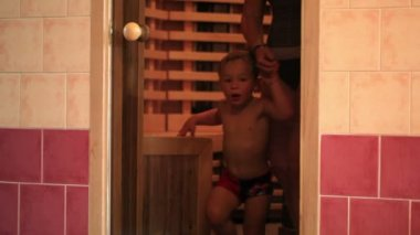 Mother and her little son coming out of sauna and closing glass door — Vídeo Stock