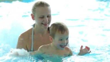 Moeder en haar zoontje spelen in ruw water van het zwembad. familieplezier in waterpark — Stockvideo
