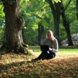 Stock Video: Young woman sitting on the lawn in the park and using her laptop. Wide shot