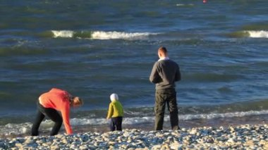 Mother, father and their little son on pebble beach throwing stones into water — Stock Video