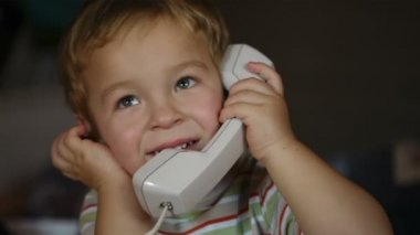 Close-up portrait of an excited Caucasian little boy talking over telephone receiver — Stock Video