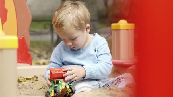 Niño jugando con el juguete en patio. — Vídeo de stock