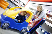 Young boy in a child supermarket trolley — Stock Photo