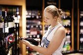 Woman reading inscription on bottle — Stock Photo