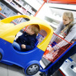 Young boy in a child friendly supermarket trolley — Stock Photo
