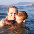 Happy mother teaching her young son to swim — Photo