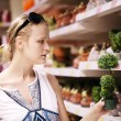 Attractive woman choosing potted plants — Stok fotoğraf