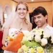 Smiling bride and groom with bouquets of flowers — Stock Photo