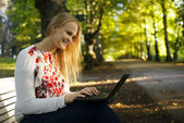 Young woman using her laptop in the park — Stock Photo
