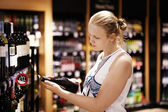 Woman reading inscription on the wine bottle in store — Stock Photo