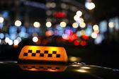 Illuminated taxi cab sign on a city street — Stock Photo