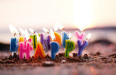 Birthday candles burning on a seashore — Stock Photo