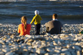 Family of three on pebble beach — Stock Photo