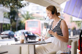 Laughing woman wearing a headset in outdoor cafe — Stock Photo